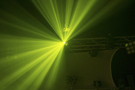 Disco light with blury green light beams shot in darkened club with smoke and stage set to rear Stock Photo