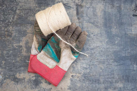 gardening gloves: A roll of gardening string and soil covered muddy gardening gloves on a black plastic muddy sheet