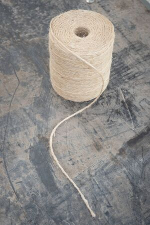 twining: A roll of gardening string on a black plastic muddy sheet