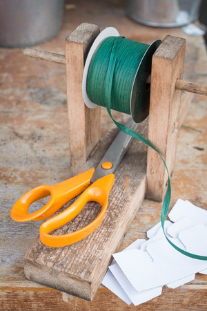 raffia: Still life photograph showing orange handled scissors, raffia and tags on a wooden bench