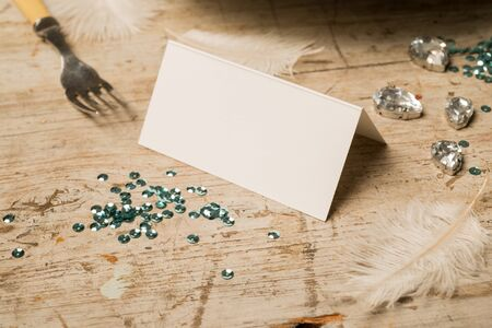 green gemstones: Blank place card surrounded by feathers, dinner fork, green sequins, and fake gemstones on a wooden surface for copy space. Stock Photo