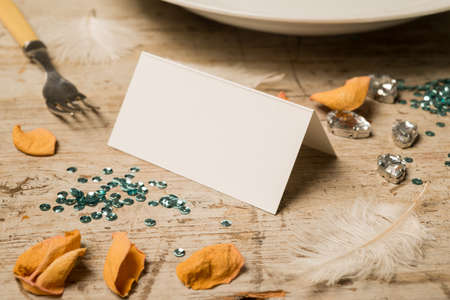 green gemstones: Blank place card surrounded by green sequins, feathers, fake gemstones, dinner fork and plate, and flower petals on a wooden surface for copy space. Stock Photo