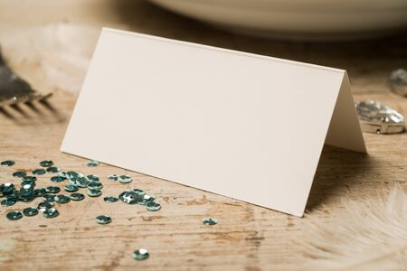 green gemstones: Closeup of blank place card along with green sequins, feathers, fake gemstones, dinner fork and plate on a wooden surface for copy space. Stock Photo