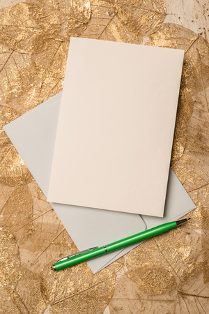 greetings card: Empty greeting or invitation card alongside a writing pen on dried leaves background for copy space.