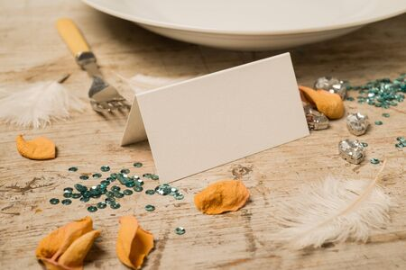 facing right: Blank place card facing right surrounded by green sequins, feathers, fake gemstones, dinner fork and plate, and flower petals on a wooden surface for copy space. Stock Photo