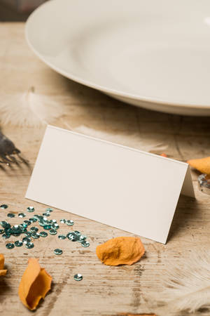 green gemstones: Blank place card surrounded by green sequins, feathers, fake gemstones, dinner fork and plate, and flower petals on a wooden surface for copy space in portrait orientiation Stock Photo
