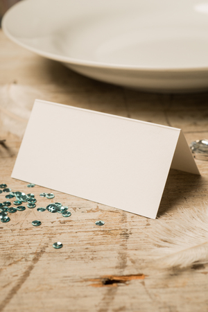 green gemstones: Blank place card along with green sequins, feathers, fake gemstones, and dinner plate on a wooden surface for copy space. Stock Photo