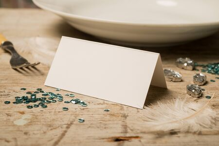 green gemstones: Blank place card along with green sequins, feathers, fake gemstones, dinner fork and plate on a wooden surface for copy space. Stock Photo