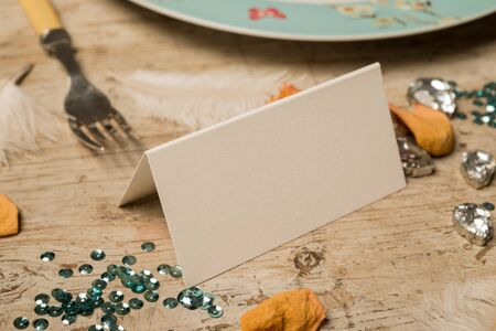 Blank place card facing right surrounded by green sequins, feathers, fake gemstones, dinner fork and printed plate, and flower petals on a wooden surface for copy space.