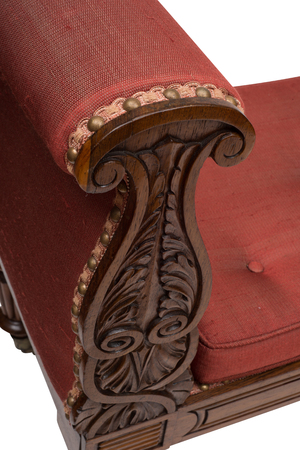 daybed: Hand-carved design on wooden arm of an antique day bed.