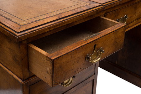 ajar: An ajar drawer of an antique solid wood office table.