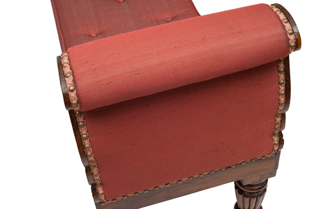 upholstered: Upholstered arm of an antique wooden daybed.