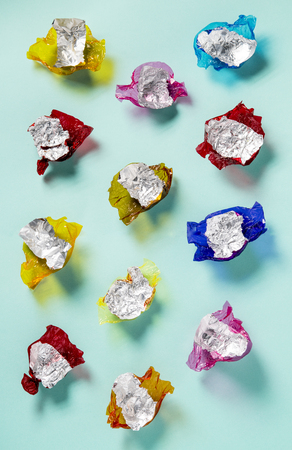 wrappers: A selection of brightly coloured sweet wrappers with foil laid out in lines on a blue grey backdrop shot from overhead with soft shadows Stock Photo