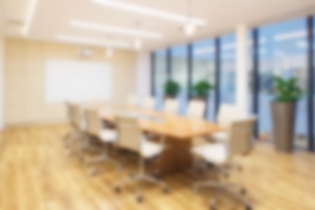 Fond de bureau défocalisé d'une salle de Conseil avec plancher en bois rustique, table de réunion et chaises eames. Banque d'images
