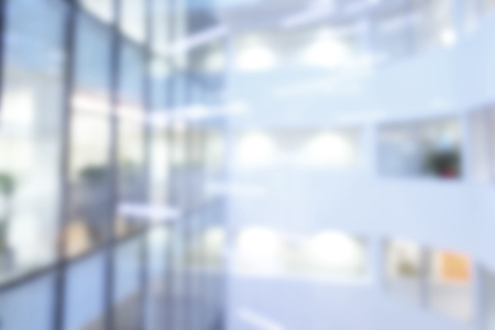 Out of focus or blurred office background of Large atrium lit by suspension lights, overlooking offices.