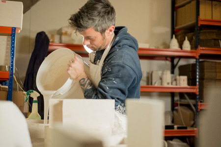 plaster of paris: A man in plaster-splattered clothing pouring plaster mixture into a mold. Stock Photo