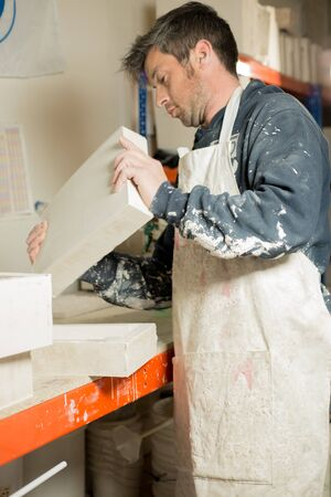 hardened: A man in plaster-splattered clothing lifting a block of hardened plaster Stock Photo
