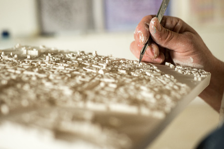 Hand with a precision knife fine-trimming a section of a 3D plaster map model Stock Photo