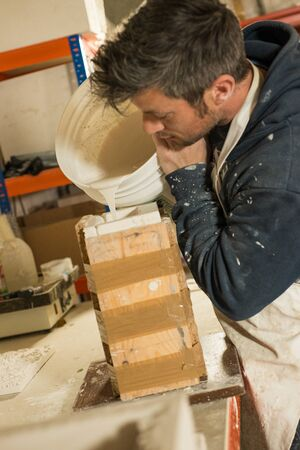 A man in plaster-splattered clothing pouring liquid plaster mixture into mold Stock Photo