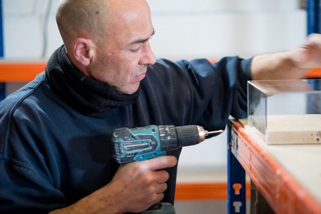 electric drill: A man with a cordless electric drill examining his work. Stock Photo