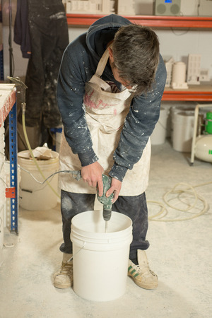stubbly: A man in plaster-splattered clothing stirring contents of a white plastic bucket using a mixer attached to an electric drill