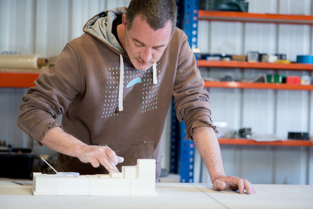 A caucasian man in brown hoodie smearing white paint on plaster model building on table.