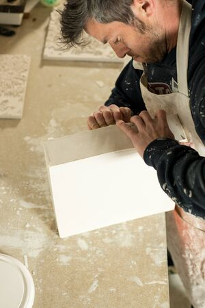detach: A man trying to detach a plaster model from mold using bare hands.