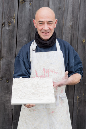 Man Presenting a Plaster 3D Model of City Map Stock Photo
