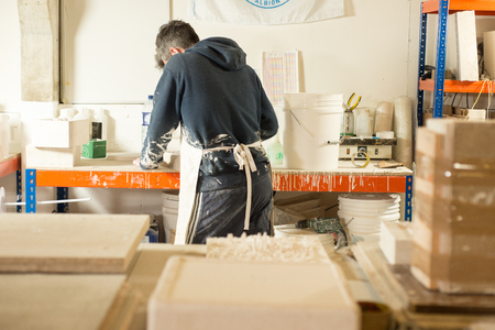 A man in plaster-splattered clothing with back turned working by a huge drafting table with plaster molds and model in the foreground Stock Photo