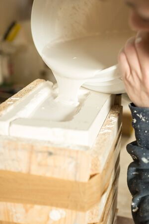 Liquid plaster flowing from bucket to a brimming mold.
