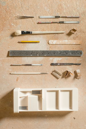 A plaster scale model building alongside tools for arts and crafts including sandpaper, files or rasps, precision blade, pincers, a pencil, paintbrushes, a popsicle stick, and a metal rule flat lay on a worn wooden surface.