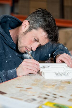 drafting table: A caucasian male in paint-splattered hoodie using a precision knife and trimming a section of a white plaster model on a desk. Stock Photo