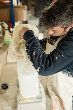 stubbly: A man pouring liquid plaster resin into a large white plastic container
