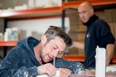 drafting table: A caucasian man in paint-splattered hoodie utilizing a precision knife to trim a plaster model while a colleague in the background looks on.