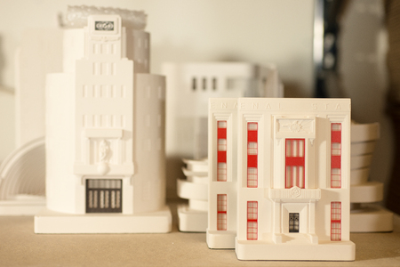Plaster scale models of well-known architectural buildings on a wooden tabletop. Stock Photo