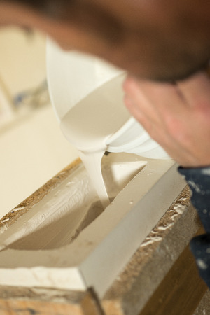 plaster of paris: Closeup of liquid plaster being poured into mold. Stock Photo