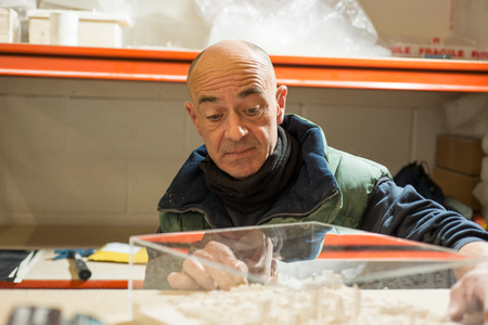 A man examining a 3D ciity model made of plaster housed in clear acrylic case. Stock Photo