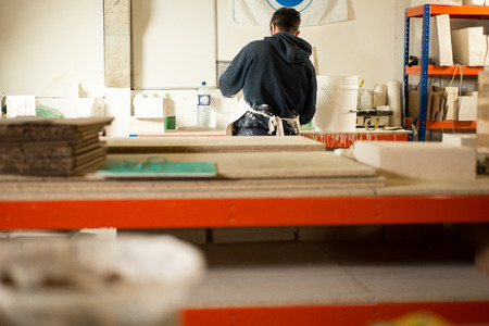 A man in plaster-splattered clothing with back turned working by a huge drafting table with plaster molds, models, and additional tables in the foreground