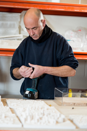 cordless: A caucasian man in a dark sweater preparing an electric cordless drill for use