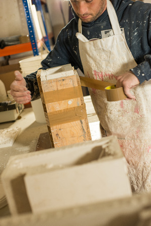 sealing tape: A man in plaster-splattered clothing assembling and sealing a plaster mold with packaging tape. Stock Photo