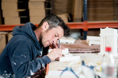 stubbly: A man in paint-splattered dark hoodie busy engraving a section of a white plaster building model using a precision knife on a drafting table.
