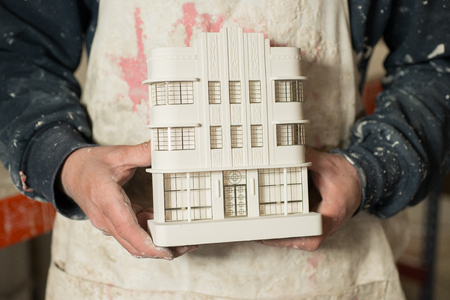 plaster of paris: A plaster scale model of a known architectural building held with two hands by some person. Stock Photo