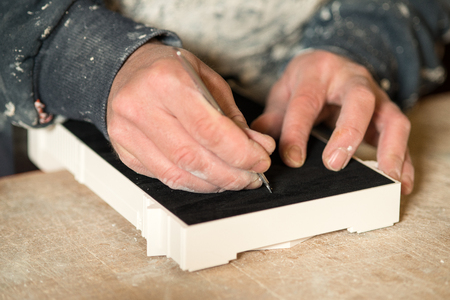 plater: A hand with a precision knife cutting a portion of black felt paper on a plater model Stock Photo