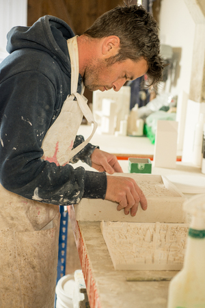 stubbly: Stubbly man examining a molded 3D city map made of plaster