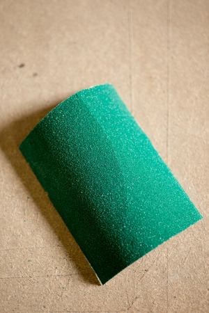 sandpaper: A piece of green sandpaper on plywood surface with copy space.