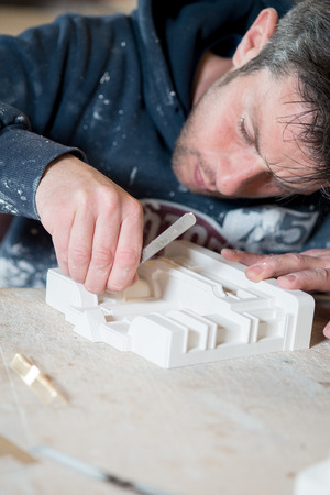 drafting table: A caucasian male in paint-splattered hoodie using a precision knife and sculpting a white plaster model on a desk.
