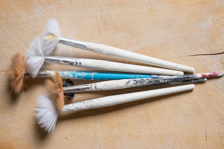 A set of used paintbrushes with plaster-splattered handles and split bristles Stock Photo