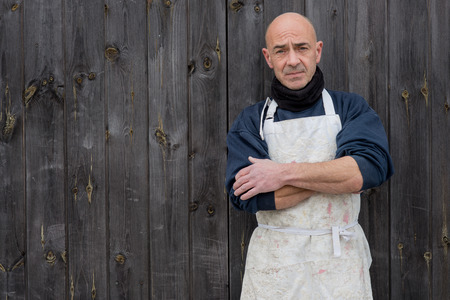 shaved head: Standing baldheaded man in thick clothing and white apron with arms crossed in a wooden panel background Stock Photo