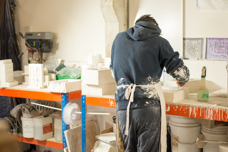 A man in plaster-splattered clothing and apron with back turned levels the surface of fresh plaster mixture on a mold using a paintbrush Stock Photo