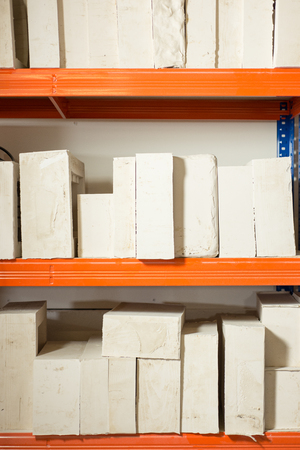 Molds for different plaster scale models arranged neatly in shelves.